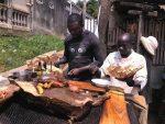 Zwei Maenner aus Kamerun bereiten Fleisch zu